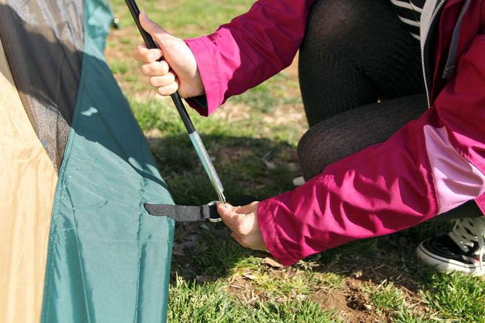 テントにポールを取り付けている女性の手元