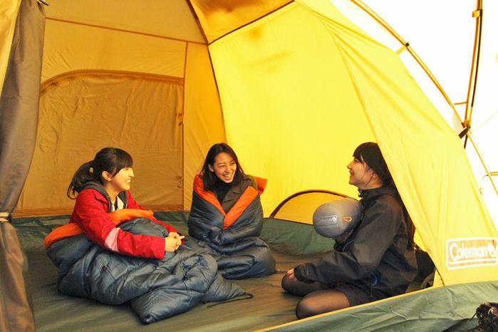 コールマンのタフドームの中で会話を楽しむ女性3人
