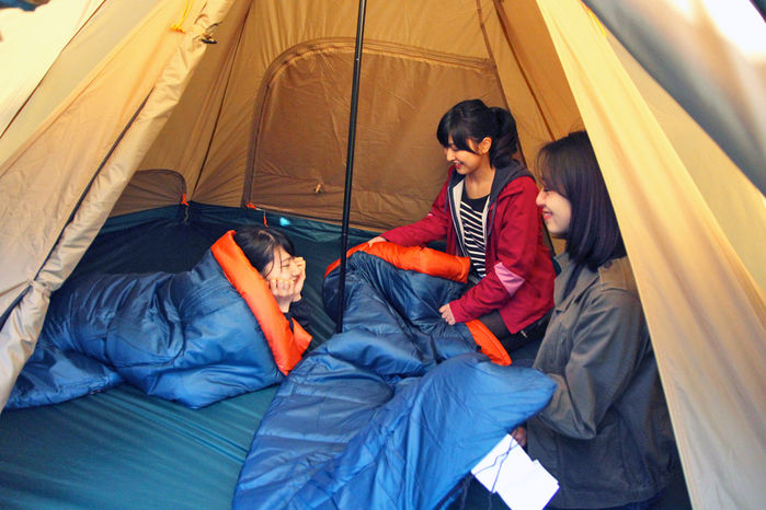 マットの上で寝袋にくるまる女性たち