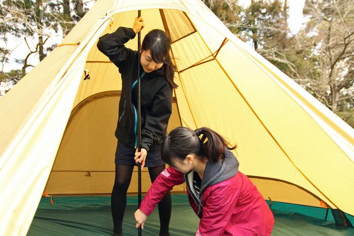 メインポールでテントを持ち上げている女性2人
