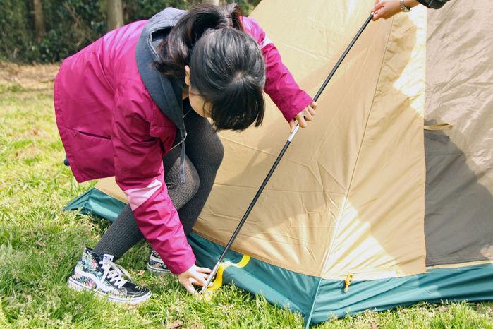 ポールをテントに取り付けている女性