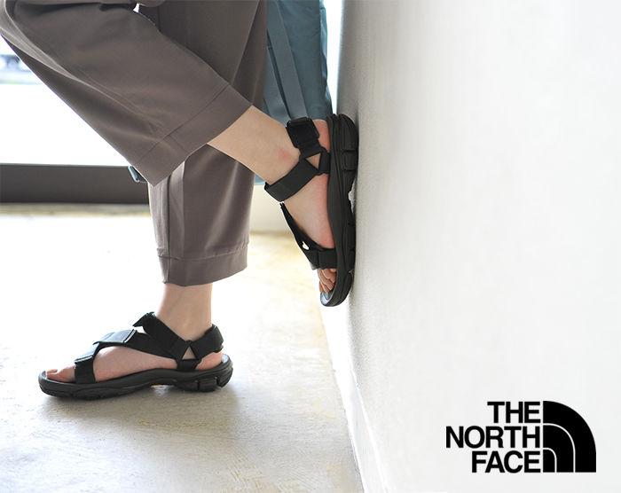ノーシフェイスのウルトラティダルサンダルを履いて壁にもたれかかった足元