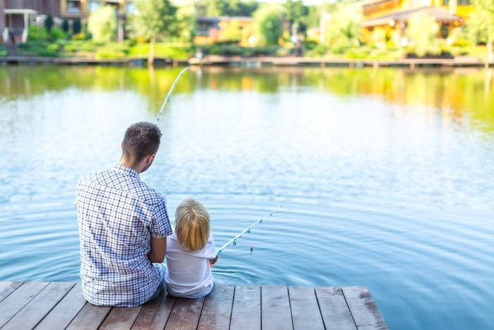 池のほとりで釣りをする親子