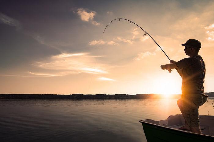 夕日の元でボート上で釣りをする男性