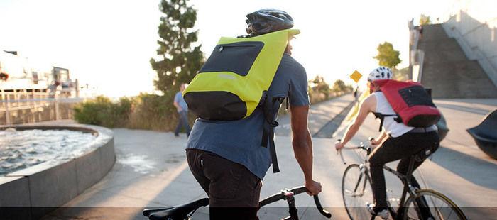 シールラインのリュックを背負い自転車をこぐ男性