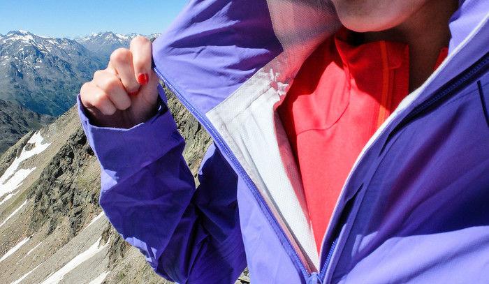 山並みをバックに襟元を広げる女性の首元のアップ