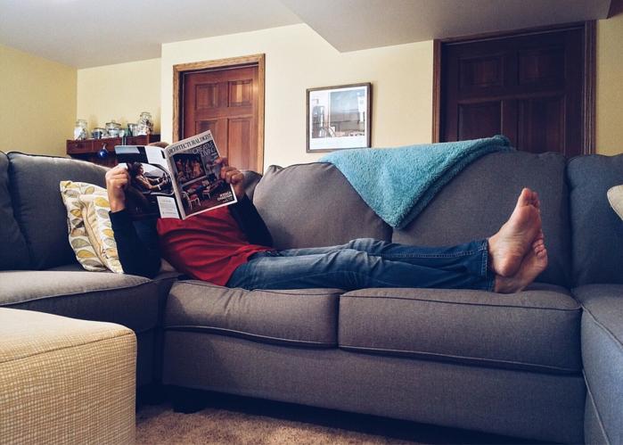 家のソファーで雑誌を読む女性
