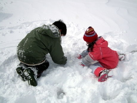 酸ヶ湯公共駐車場で雪遊びをする子供