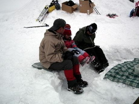雪原にレジャーシートを敷いて座る親子