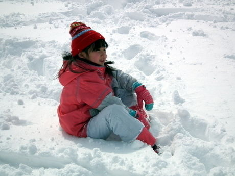 積もった雪に座る子供