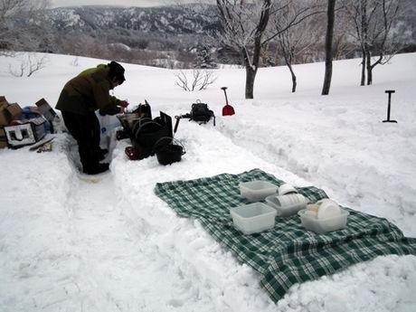 雪製ピクニックテーブルの隣で調理する様子