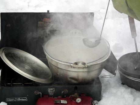 雪原の中で料理する様子