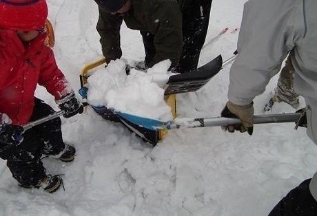 スノーショベルで雪を集める様子