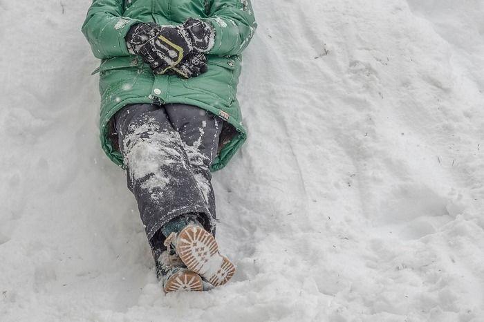 雪がついたスノーウェアを着て雪の上に寝転ぶ人
