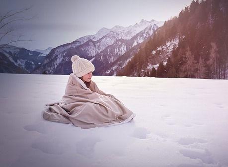 雪原で毛布にくるまる子供
