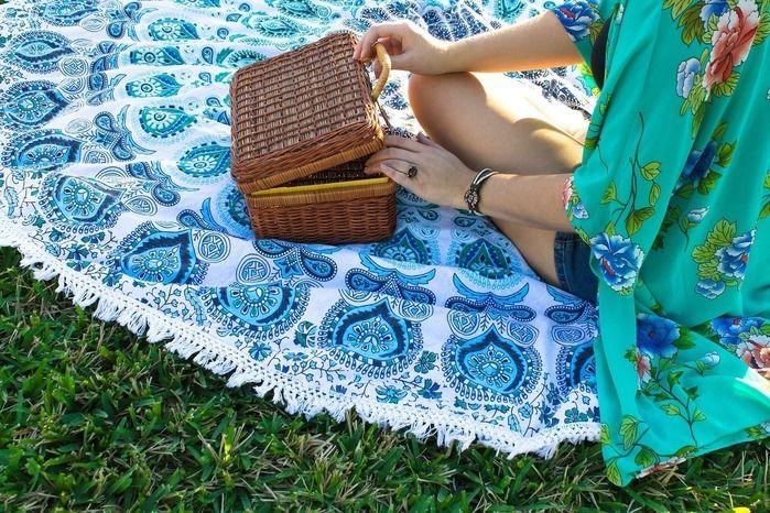 ピクニックラグの上でピクニックバスケットを開く女性