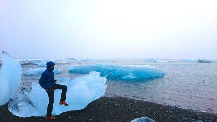 氷河の上に腰掛けるマウンテンパーカーを着た男性