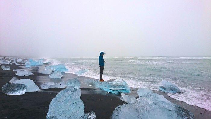 氷河の流れついた砂浜に立ち、海を見つめるマウンテンパーカーを着た男性