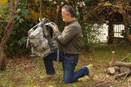 バックパックを膝の上に載せる男性