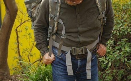 バックパックのショルダーパッドのストラップをしめる男性