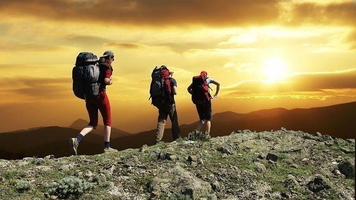 夕日が沈む山に登る男性たち