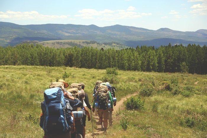 バックパックを背負い草原を歩く人々