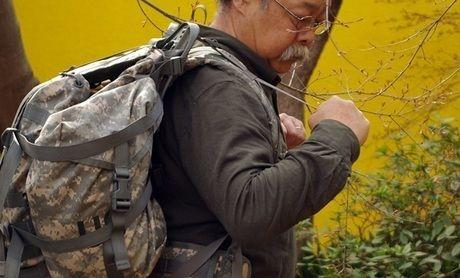 バックパックのショルダーアシストベルトを締める男性