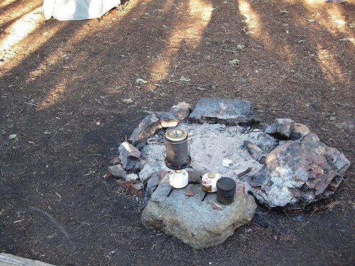 石の焚き火台においたキャンプ用ケトル