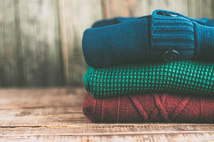 カラフルなセーターをたたんで積み重ねた様子