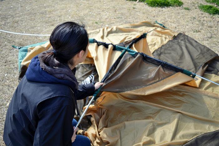 コールマン タフドーム/240のポールを通す女性