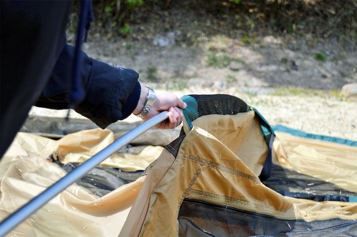コールマン タフワイドドームⅣ/300にポールを通す女性