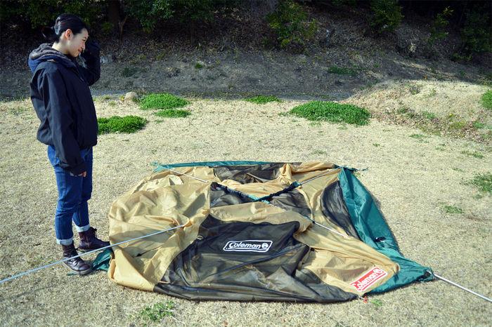 コールマン タフドーム/240のポールが通されたテントと女性