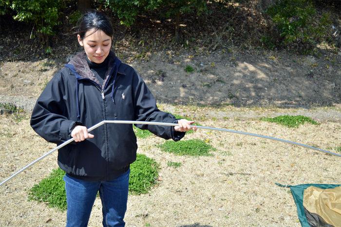 コールマン タフドーム/240のポールを組み立てる女性
