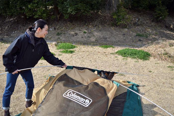 コールマン タフドーム/240のポールを持ち上げる女性
