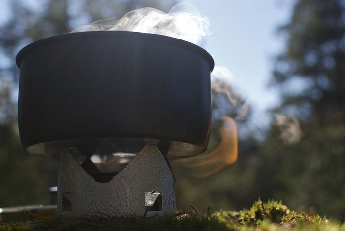 自然の中、クッカーで料理をする様子