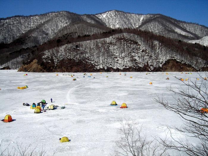 雪山のふもとでワカサギ釣りのを楽しむ人々