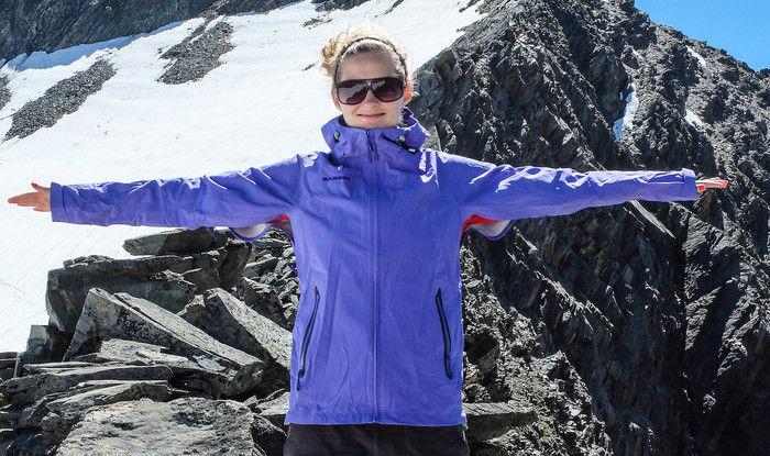 岩山を背景に手を広げて写真をとる女性