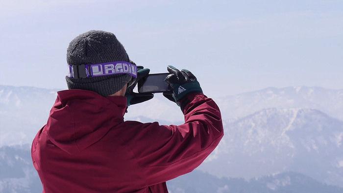 山の風景をスマホで撮影する人