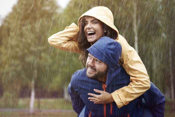 雨の中でレインウェアを着ておんぶをする男女