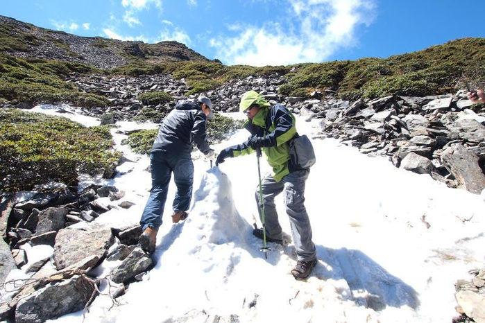 雪が積もった山を登る男性
