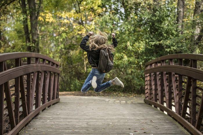 橋の上でジャンプしているリュックを背負った女性