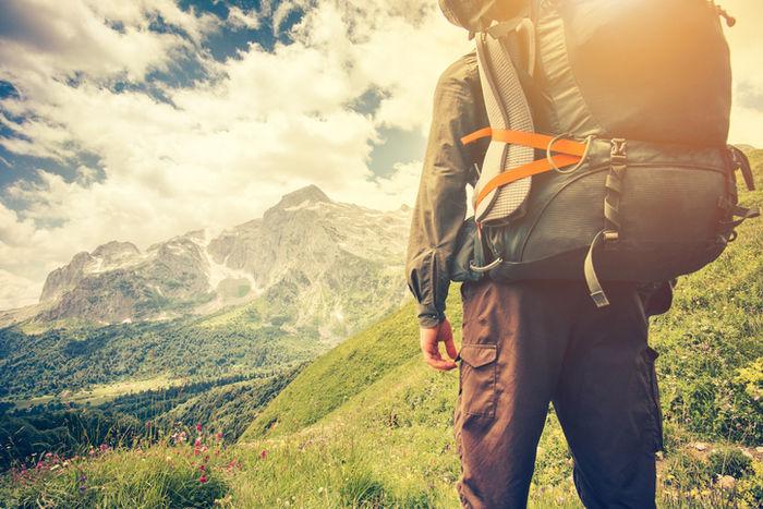 重い荷物を背負って頂上を見つめる男性