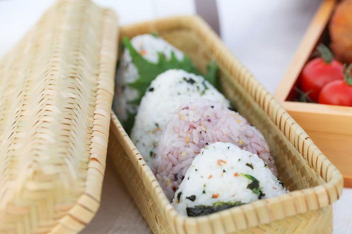竹カゴのお弁当箱に入った混ぜ込みおにぎり
