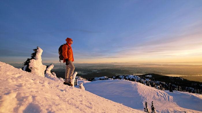 雪山から日を眺める人