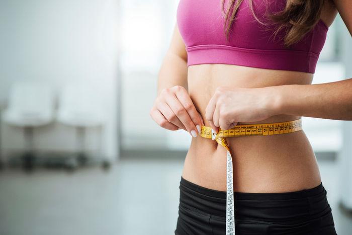 ウエストでメジャーを測る女性の腹部
