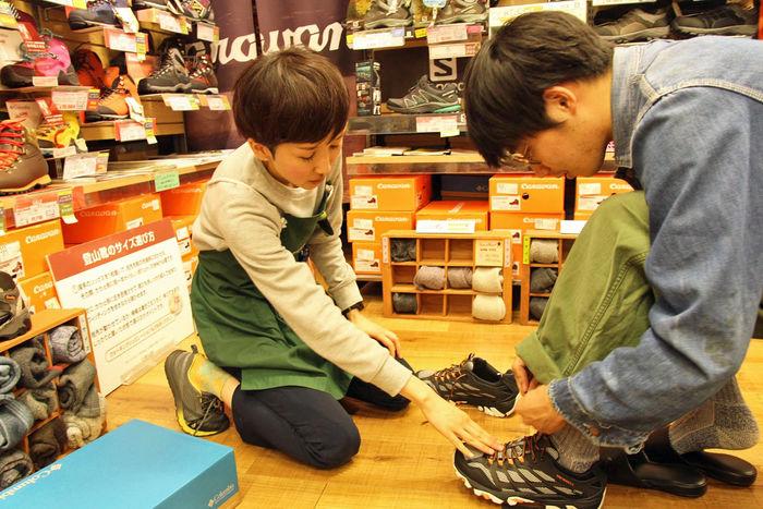 商品の説明をするエルブレス吉祥寺店地下1階、シューズフロア担当の大津さん