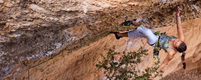 険しい砂壁を登る女性