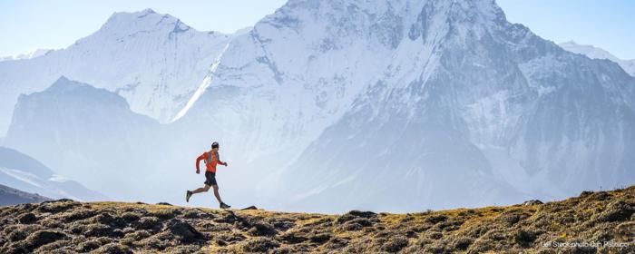 雪山をバックに走る男性