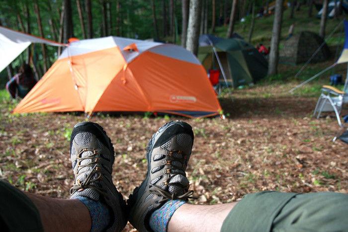メレルのトレッキングシューズを履いた足元とテント