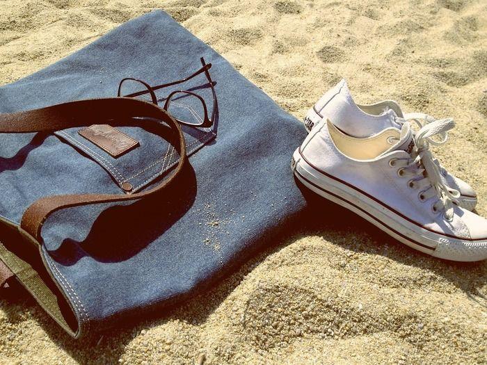 砂浜に置かれたカバンとスニーカー